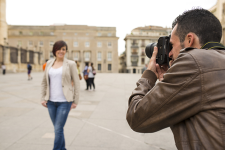 Man taking touritst picture of attractive woman in public place with reflex camera 스톡 콘텐츠