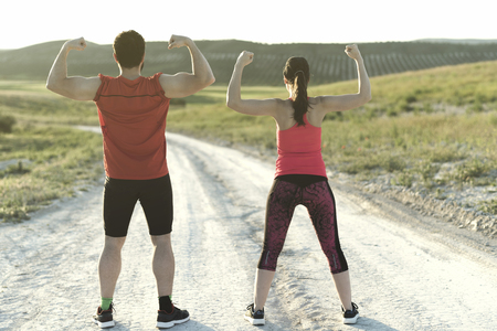 Training couple in outdoors image posing muscles