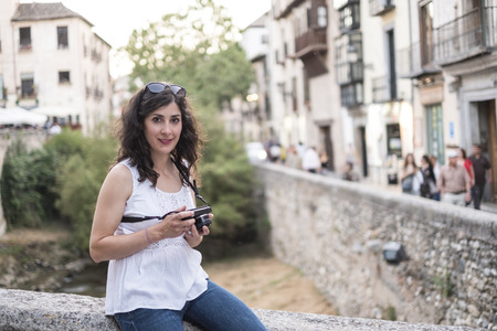 Granada, Spain. Tourist woman with mirrorless camera in darro bridge looking at camera. Stok Fotoğraf