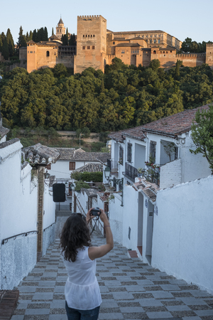 woman taking picture to the alhambra in sunny day