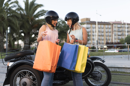 Two happy sister blonde women on sidecar bike smiling and happy Stock fotó