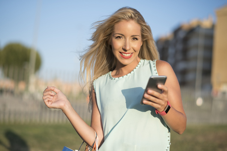 Woman in park looking smartphone after shopping