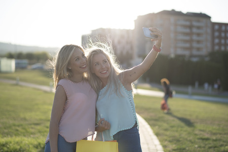 Happy sisters taking selfie after shopping in sunset image