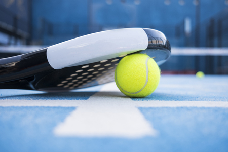 Racket and padel balls on the blue court. Фото со стока