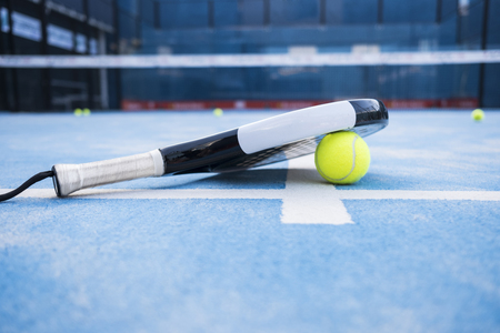 Racket and padel balls on the blue court. 免版税图像