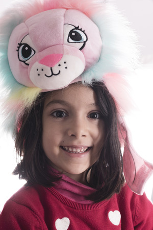 Cute girl portrait with lion muppet hat looking at camera isolated on white