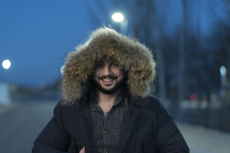 man with fox fur parka coat poses during the blue hour on a winter night