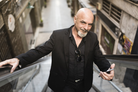 Senior business man in scalator with smartphone Imagens