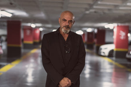 Senior mature man posing in parking looking at camera with suit