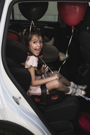 cute little girl with ballons on car chair very excited and happy looking at camera