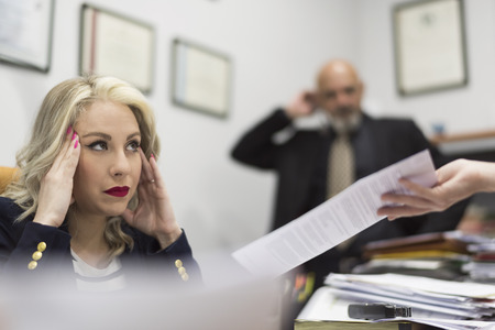 Female office worker stressed before a large load of documents and office work Imagens