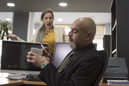 senior suit man ready for smoke cigar in workplace and angry woman nagging his attitude