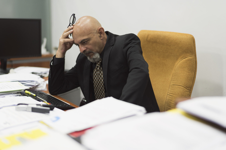 Mature and elegant man stressed or sick during work with large accumulation of documents Stock Photo