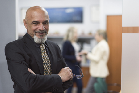 senior man portrait posing in office smiling with suit clothes, blurowner, people in background