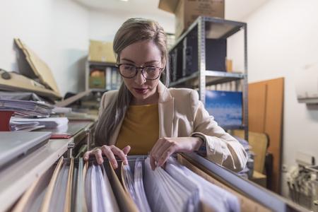 grand angle de jolie femme de bureau travaillant à la recherche de fichiers au sous-sol