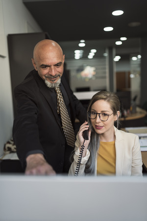 Senior man worker and beauty young woman at computer working together Stock Photo