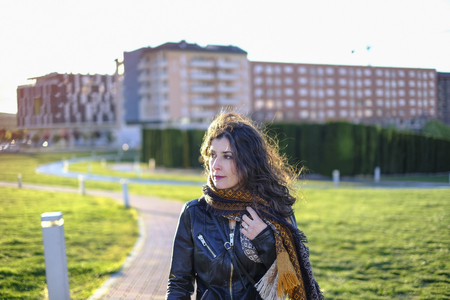 winter beauty woman portraits, walking in city with scarf and leather jacket Imagens