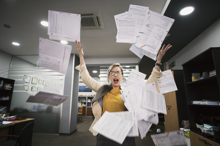 Stressed woman throws papers in the office in an image of relief