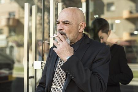 Il capo fuma un sigaro durante una pausa e i colleghi lo vedono attraverso la porta a vetri Archivio Fotografico