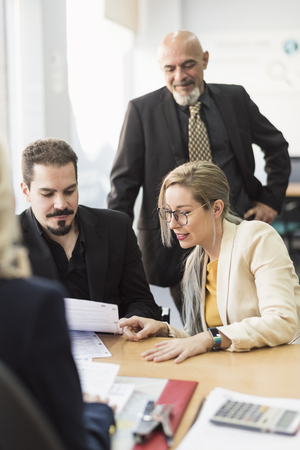 Group of workers in office looking papers in workplace