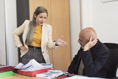 Woman scolds and warms mature man during work Stock Photo