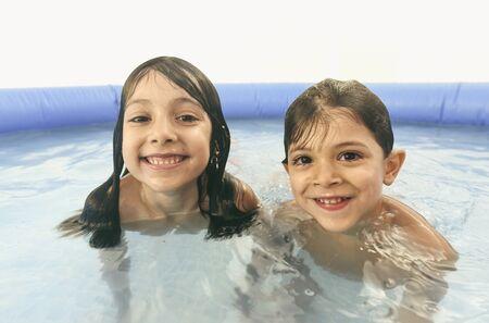 Siblings playing in plastic swimming pool looking at camera Stock fotó