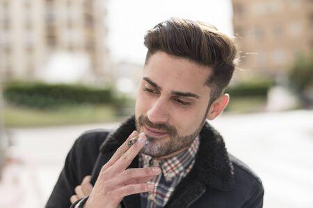 Hombre guapo fumando cigarros en la calle