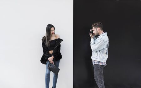 Young man photographing woman, he is on black background and she on white background