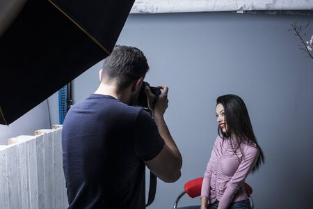 Photographer in studio shot taking beauty wman pictures