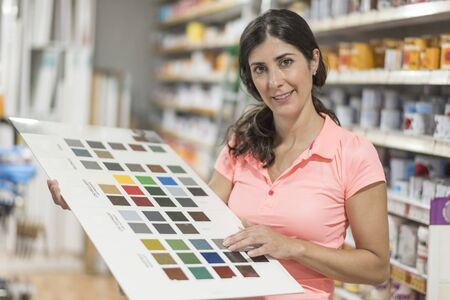 専門店で塗料カラー見本を持つ女性は、色の異なる色合いを見ます 写真素材