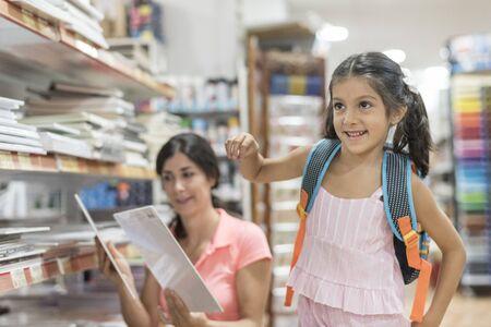 Mutter und Tochter im Laden, die Material für den Schulanfang im stationären Ladenbasar auswählen