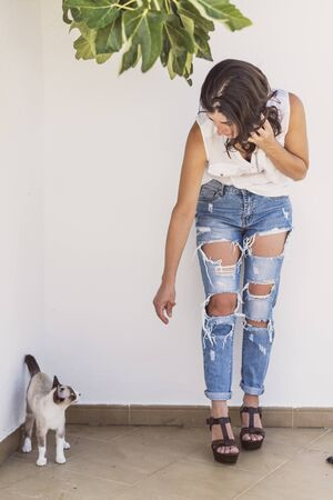 pretty mature woman with modern style with broken jeans posing with cat