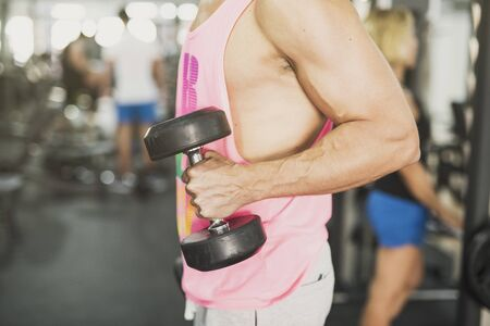 anonymous man training biceps indoors in club