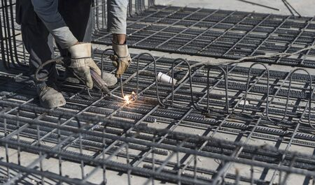 man working in outdoors image welding structures for after apply cement on and make concrete houses 스톡 콘텐츠