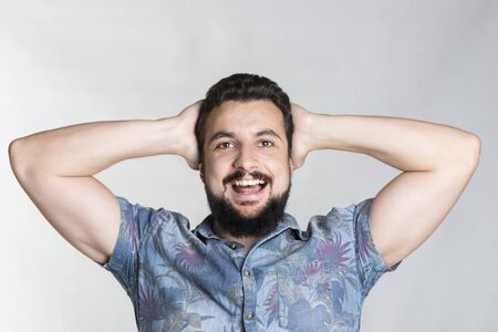 Bearded man with surprise expression in studio shot and hawaiian shirt