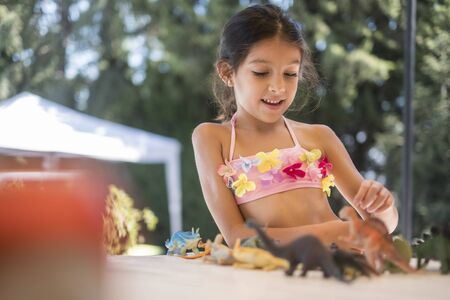 Little girl playing with dinosaurs at home outdoors Standard-Bild