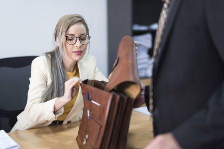 Pretty woman looking in office briefcase in office Archivio Fotografico - 129991397