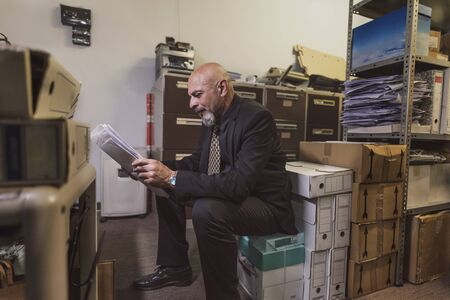 mature man in office file warehouse rests sitting on a box and checks documentation in his enterprise