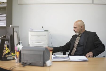 Senior Man looking computer at work, side view 스톡 콘텐츠