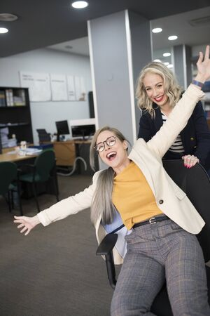 office worker pushes companion and they play at work with the chair and smiling