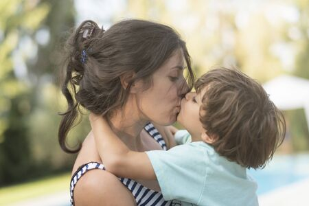 Mother kissing son in garden outdoors images in summer day