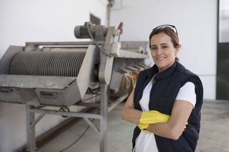 Woman posing near to machine conveyer belt for olives packaging
