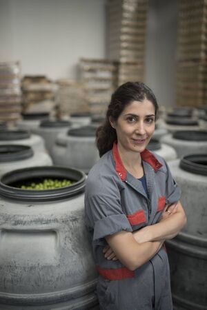 Posing worker woman in barrel with olives looking at camera