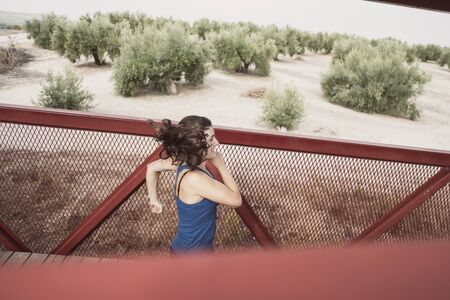 mid adult woman running on a red bridge training speed