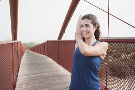 mid adult woman warming up on a red bridge before and after run