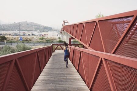 mid adult woman running on a red bridge training speed Stok Fotoğraf
