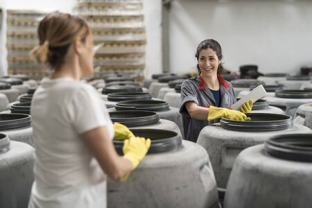 Women controlling olives fermentation and quality in barrels
