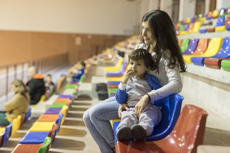 mother and son in bleachers looking sport event together 版權商用圖片