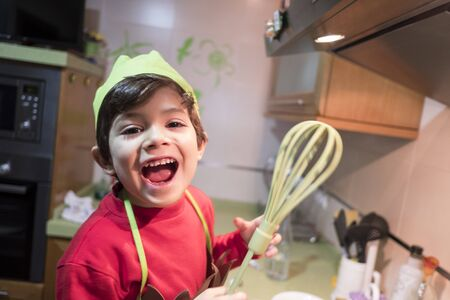 smiling cute 4 year old boy cooks macaroni at home with chef costume