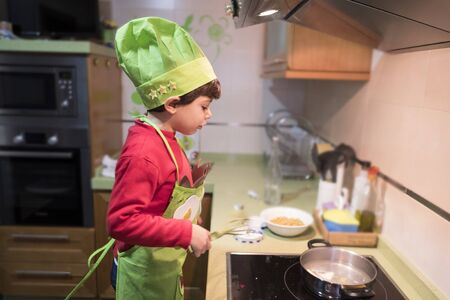 4 year old boy cooks macaroni at home with chef costume